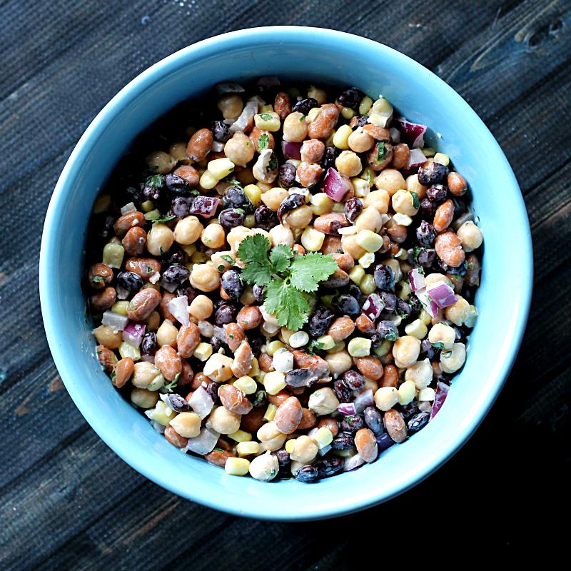 Three bean party dip in a blue bowl.