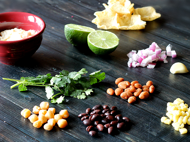 Chick peas, black beans, corn, pinto beans, red onions, cilantro, garlic, limes, tortilla scoops and dressing.