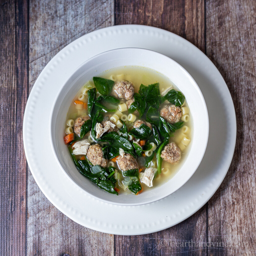 Bowl of wedding soup with meatballs, chicken, pasta, and spinach.