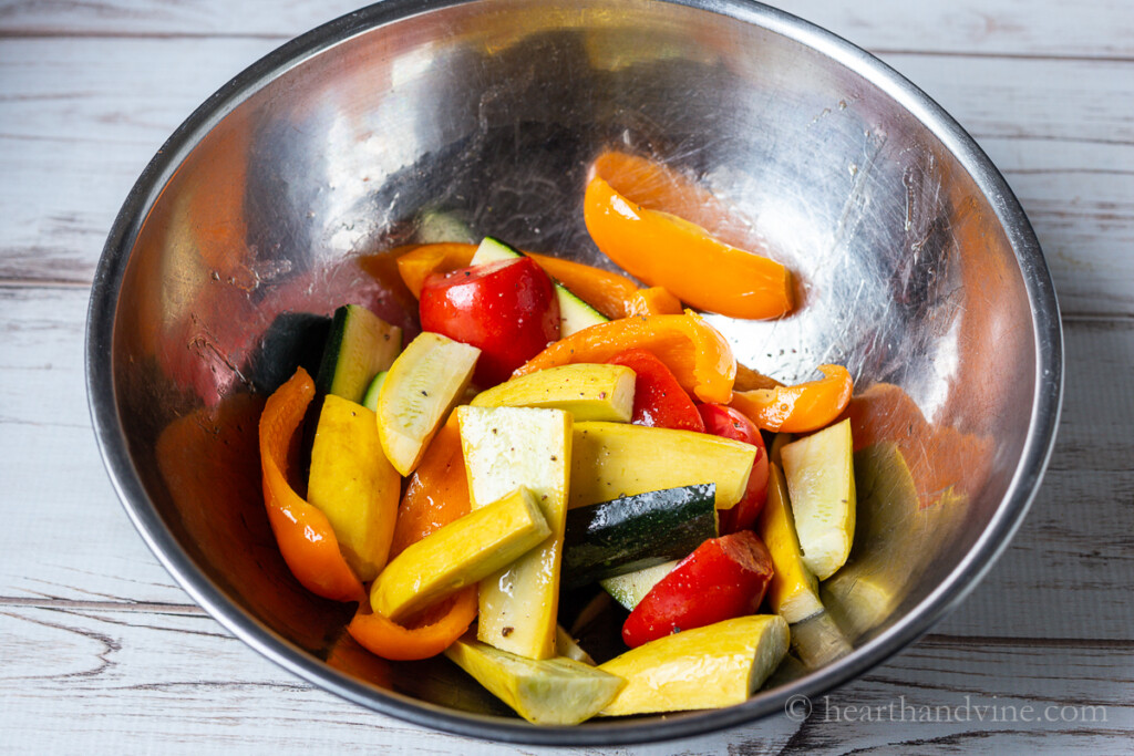 Fresh raw vegetables in a metal mixing bowl with oil, salt and pepper.