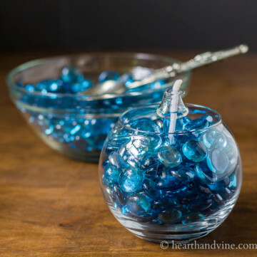 Blue gems in glass vase with lantern insert in the middle and a bowl of blue gems in the background