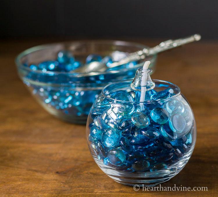 Blue gem patio oil lantern with bowl of blue gems behind.