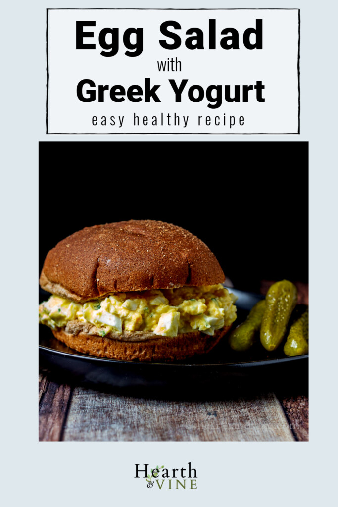 Greek yogurt egg salad on a whole wheat roll with pickles on the side