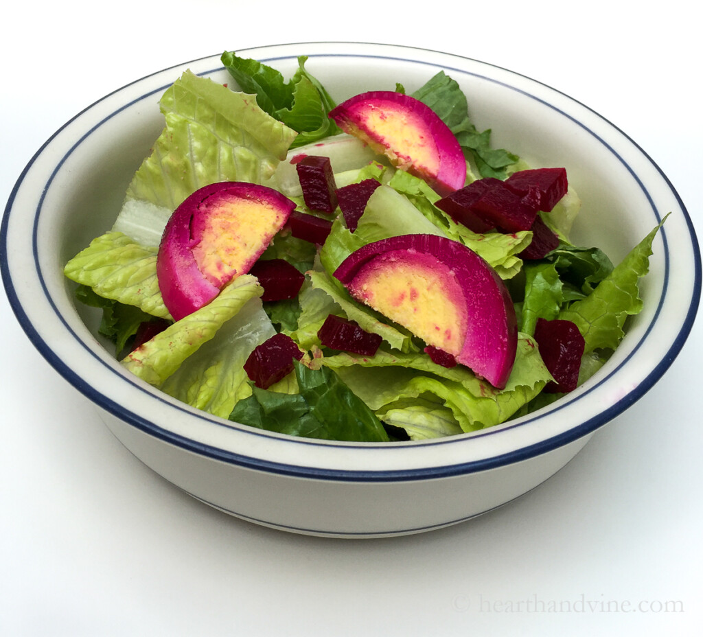 Salad bowl with lettuce, diced pickled red beets and pickled eggs sliced.