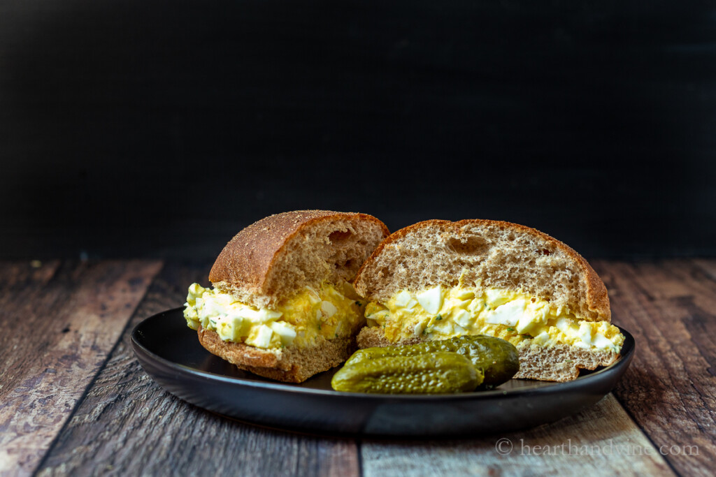 Low calorie egg salad on a whole wheat bun with dill pickles on the side.