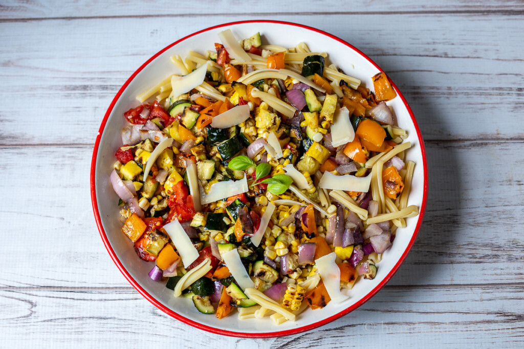 Grilled vegetables tossed with short pasta and grated Parmesan cheese in a large serving bowl.