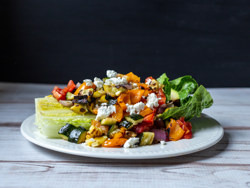 Grilled vegetable salad plate with romaine lettuce wedge topped with chopped vegetables and goat cheese crumbles.