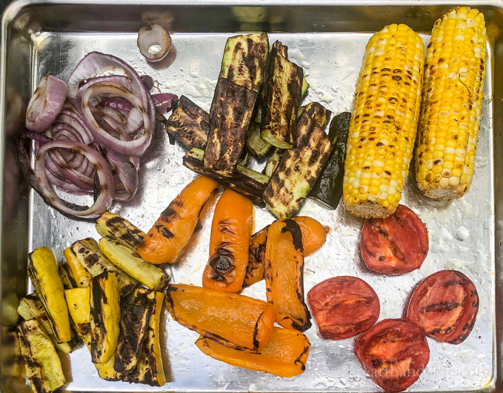 Tray with grilled red onions, zucchini, corn on the cob, yellow squash, orange peppers and tomatoes.