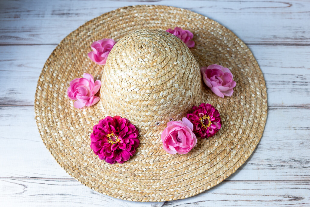 Large straw hat with a few large pink and fuchsia colored fake flowers around the rim.