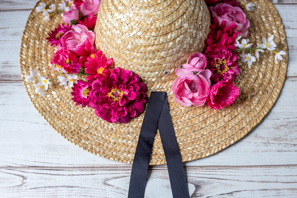 Straw hat with a wide rim covered in flowers with a piece of black ribbon tails glued in center.