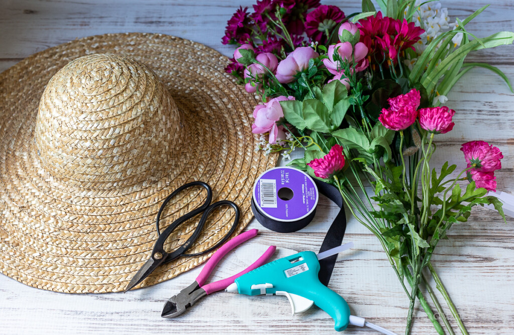 Straw hat, glue gun, glue sticks, floral shears, wire cutters, black ribbon and faux flower stems in shade of pink.