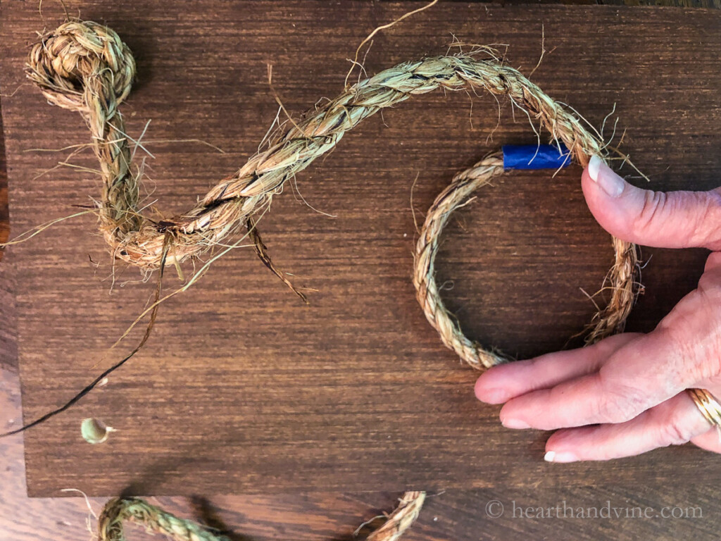 Underside of wood board with sisal rope thread through and tied into a knot.