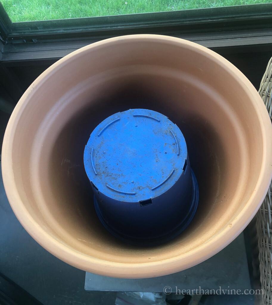 A blue plastic pot set upside down inside a large clay pot.