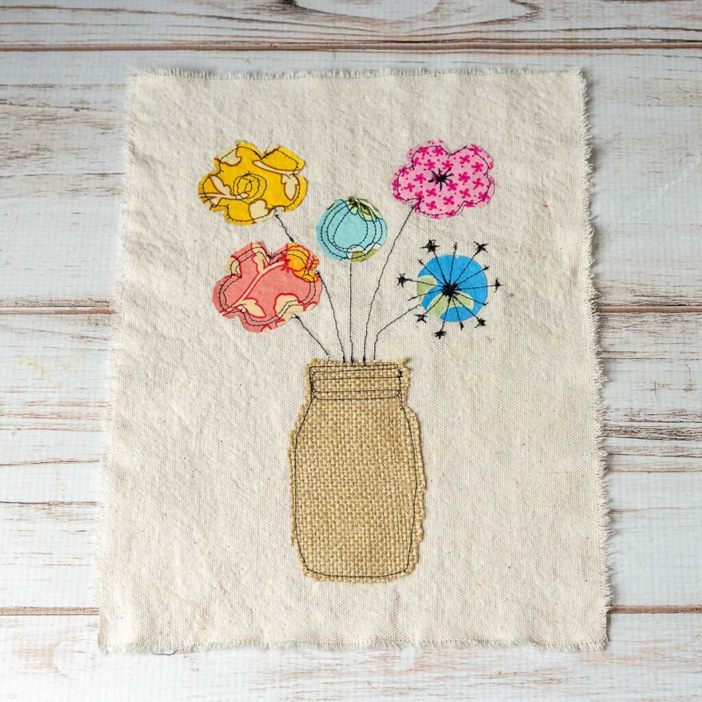 A mason jar vase with flowers in a raw applique style.