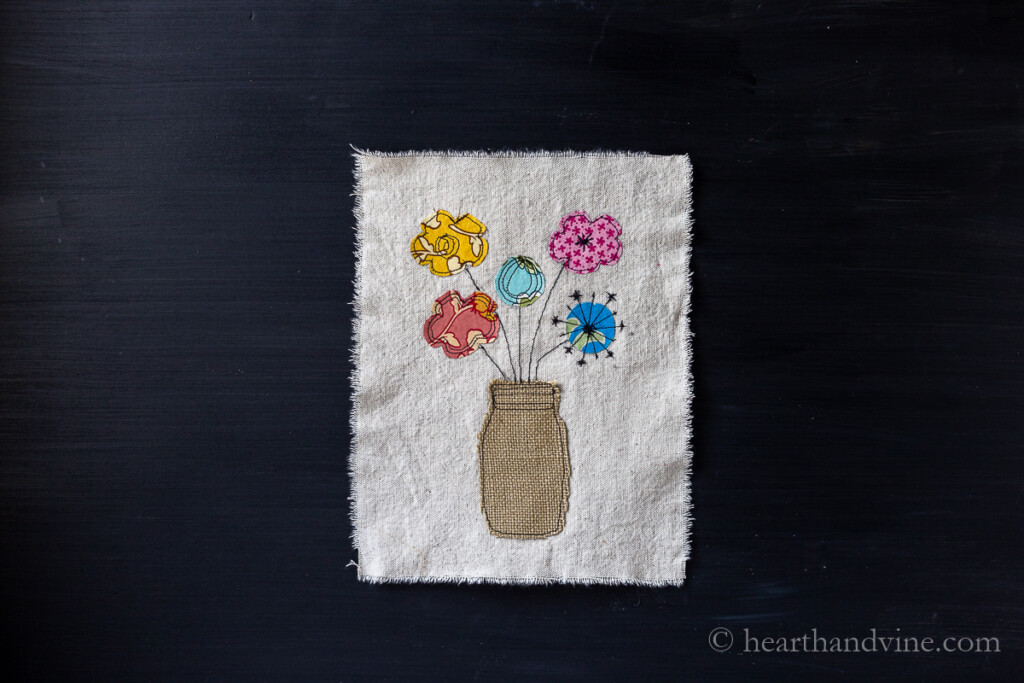 Raw edge applique effect on a drop cloth fabric of a burlap mason jar vase with colorful scrap cotton fabric flowers.