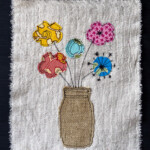 Raw edge applique of a jar of flowers.