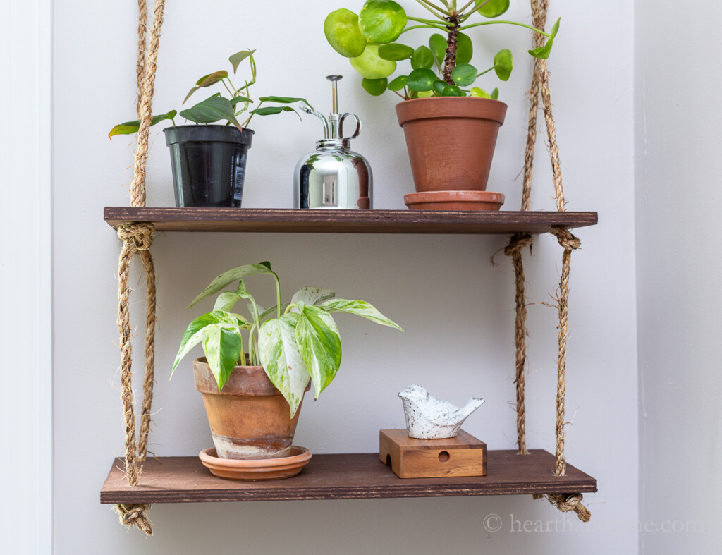 Rope shelves hanging on the wall with plants, a silver spray can, a white ceramic bird and a wooden box.