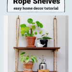 Two shelves hanging on wall with rope. Plants, a ceramic white bird and a wood box are on the shelves.
