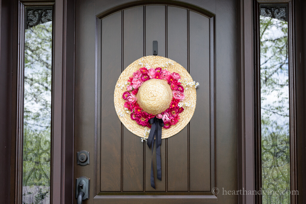 Shades of pink artificial flowers around the base of a straw hat and a black ribbon handing on the front door as a summer wreath.