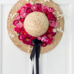 Hot pink flowers on a straw hat with a black bowl hanging on a white door.