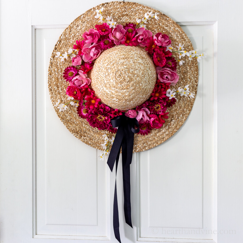 Straw hat with pink flowers on a white door.