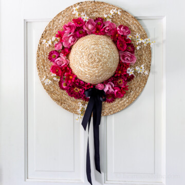 Straw hat wreath with pink and red flowers and a black bow.