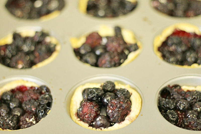 Muffin tins filled with pie crust and a combination of blueberries and blackberries.