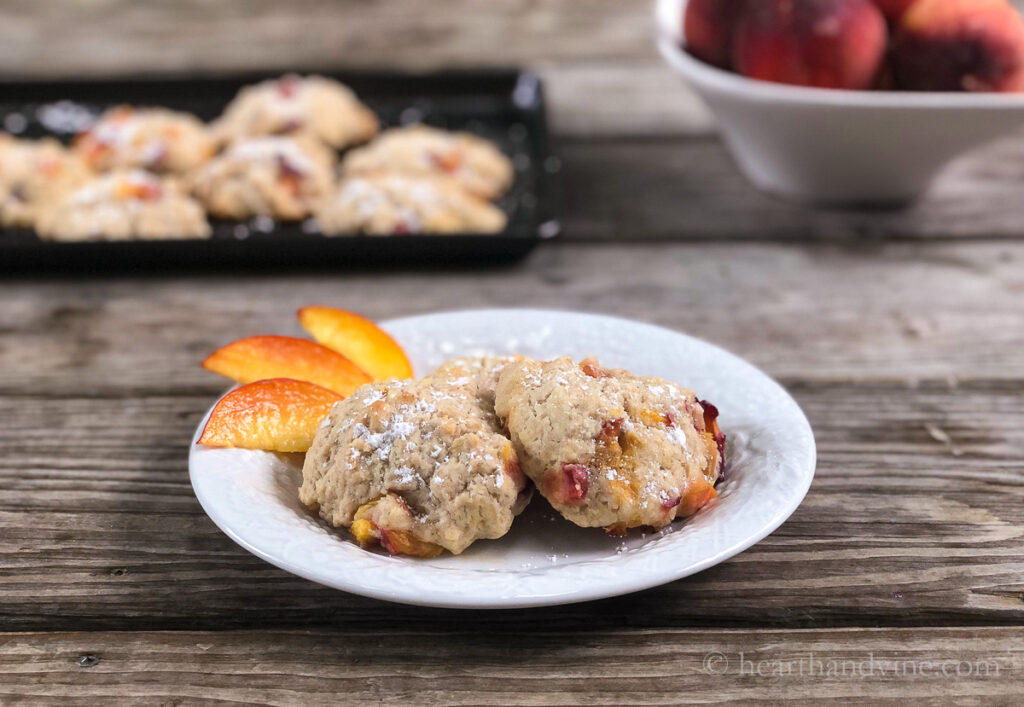 Two baked peach fritter on a plate with slices of peaches on the side.