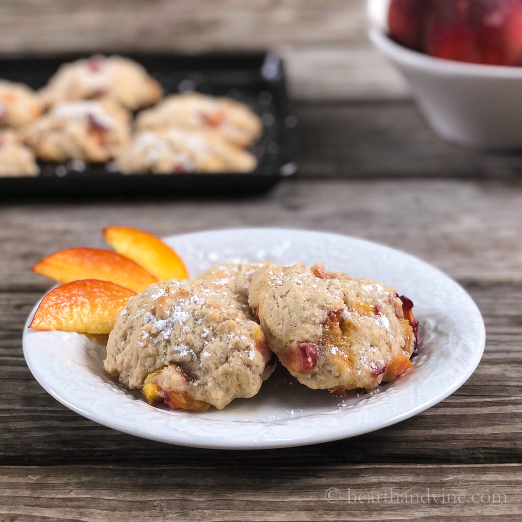 Homemade baked peach fritters on a plate with a side of sliced peaches.