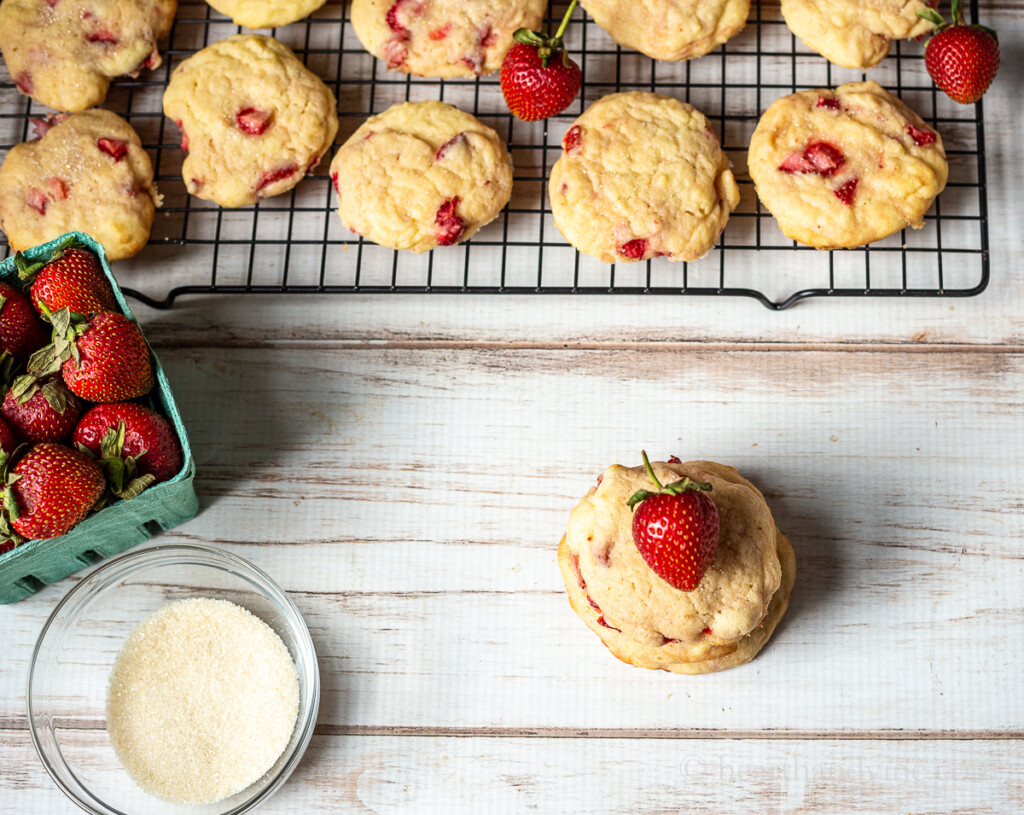 Cooling rack with cookies, fresh strawberries a market pint of strawberries, dusting sugar in a bowl.