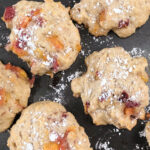 Peach fritters on a baking sheet dusted with powdered sugar
