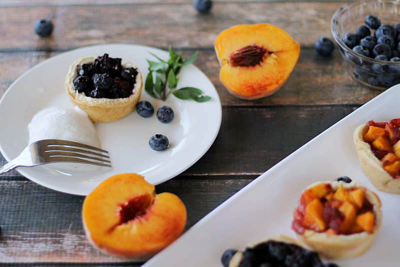 Mini muffin pies with blueberries and peaches and fresh peach halves and blueberries on a table.