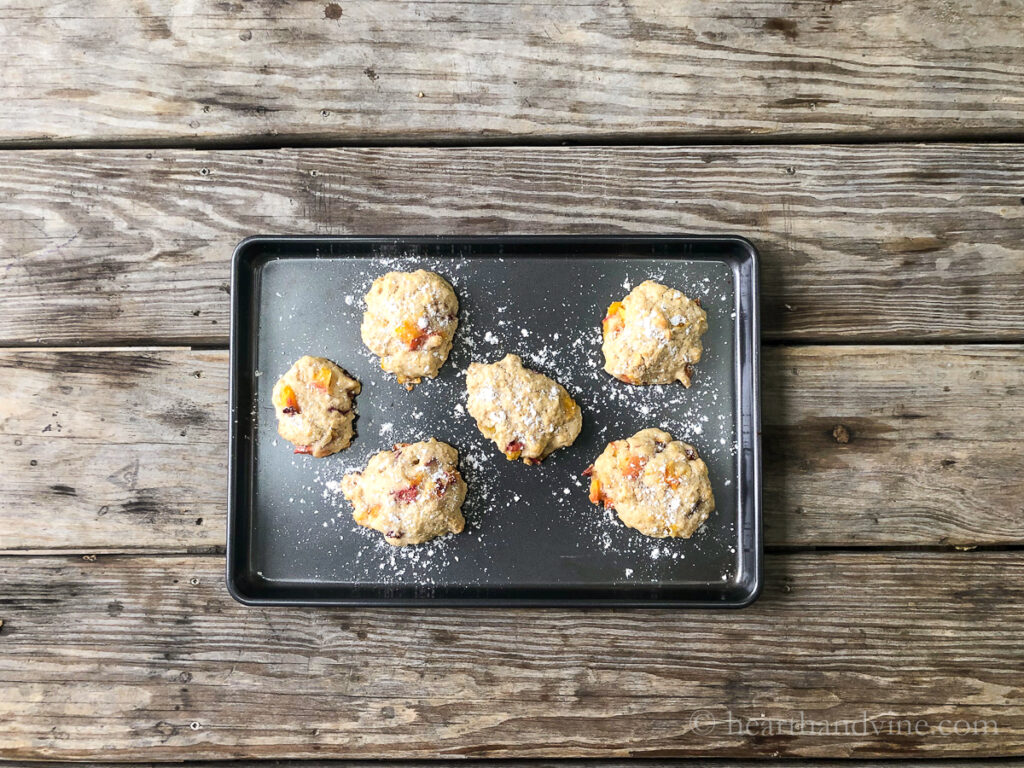 Peach fritters on a baking sheet dusted with powdered sugar.