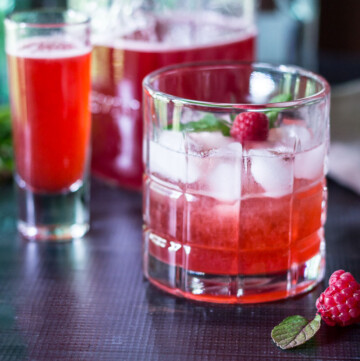 Glass with a raspberry shrub cocktail, a fresh berry and mint