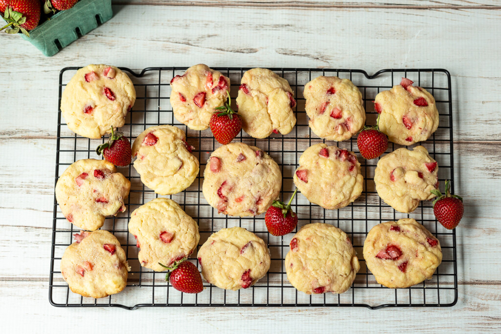 Strawberry cookies on a cooling rack with fresh berries.