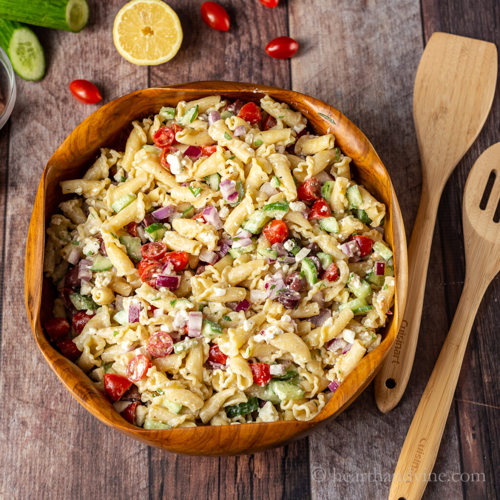 Salada de massa grega em uma tigela de madeira com dois talheres de madeira, limão, tomate uva e pepino ao lado.