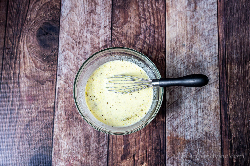 Tigela de molho cremoso de salada de massa grega e um batedor de arame.