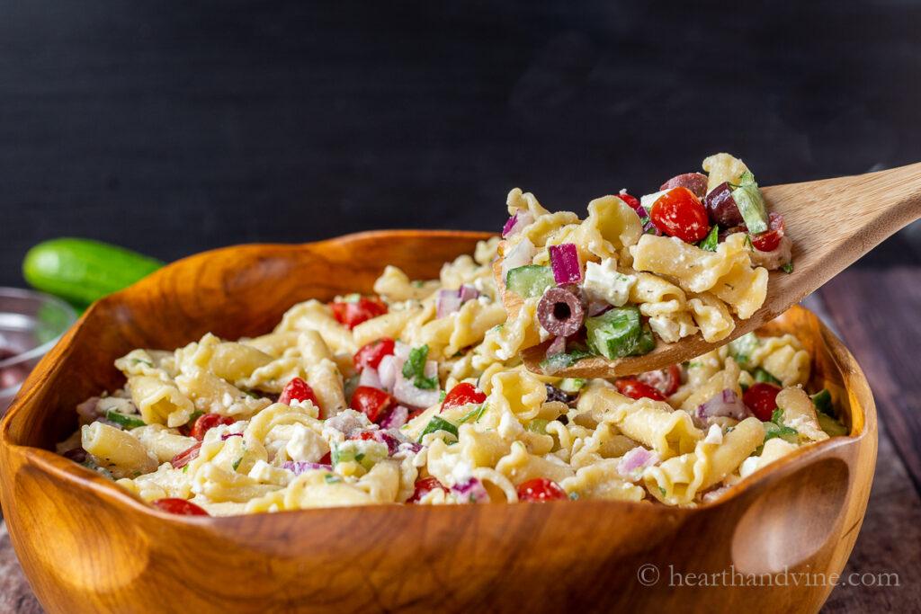 Colher de salada de massa grega saindo de uma tigela grande de madeira.