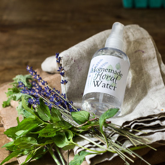 Spray bottle of floral water with fresh lavender and mint on a linen towel.