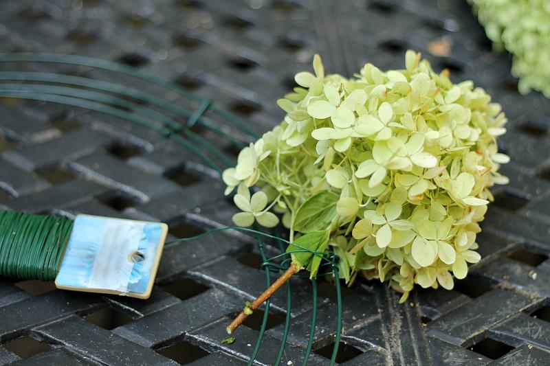 Uma flor de destaque com um arame floral enrolado em volta da haste presa a uma pá de arame.