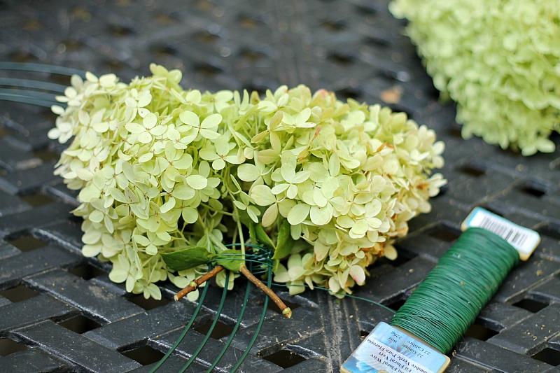 Flores de hortênsia em destaque presas a uma armação de guirlanda de arame com arame de remo floral.