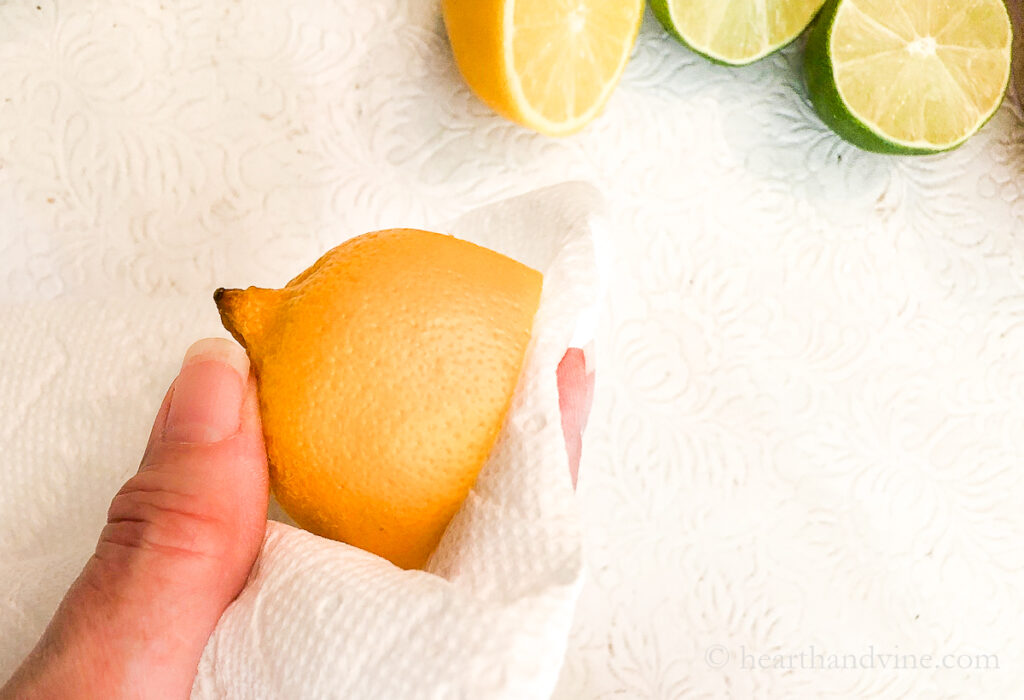 Half a lemon with a paper towel blotting off the juice on the cut side.