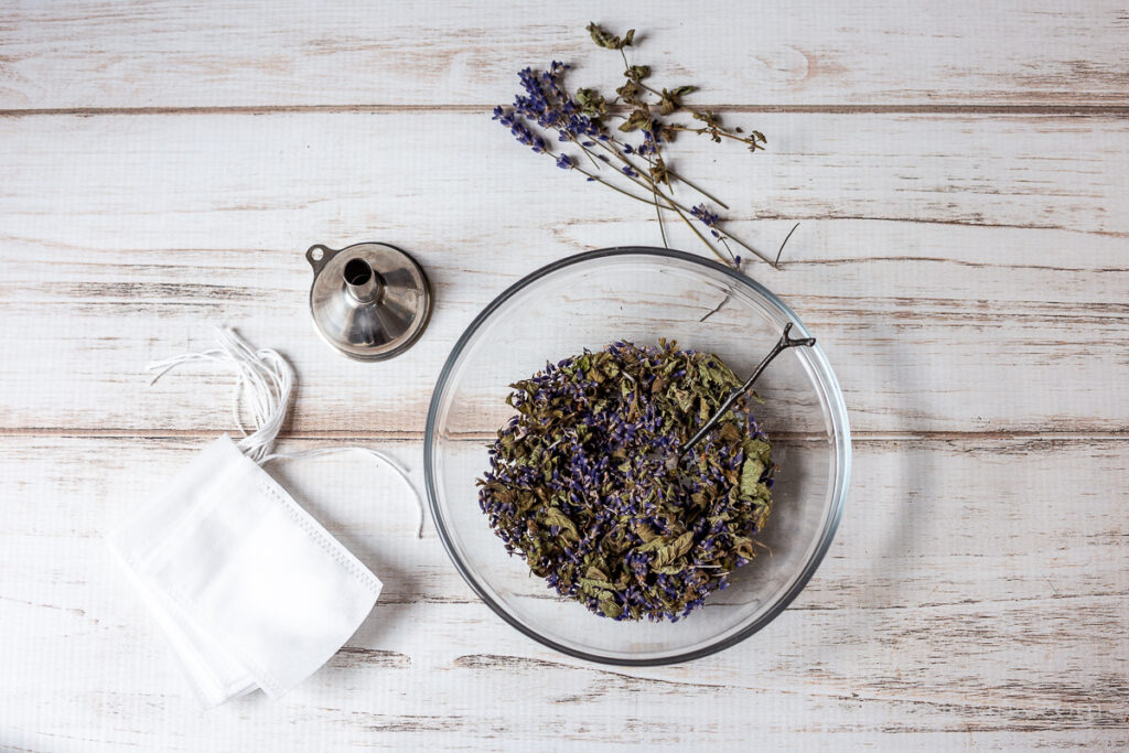 Bowl of dried lavender and lemon balm. A small metal funnel and a stack of tea filter drawstring bags.