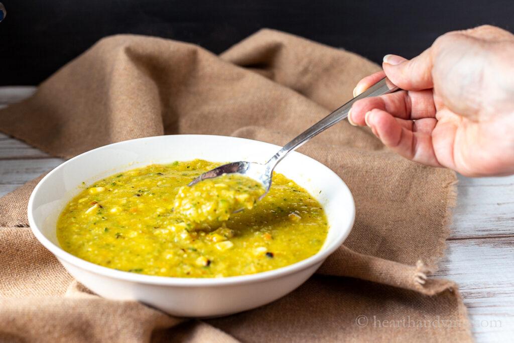 Tigela de sopa de milho com abobrinha e uma mão pegando uma colher cheia.