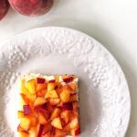 Uma porção de barras de cheesecake de gengibre e pêssego em um prato ao lado de pêssegos frescos.
