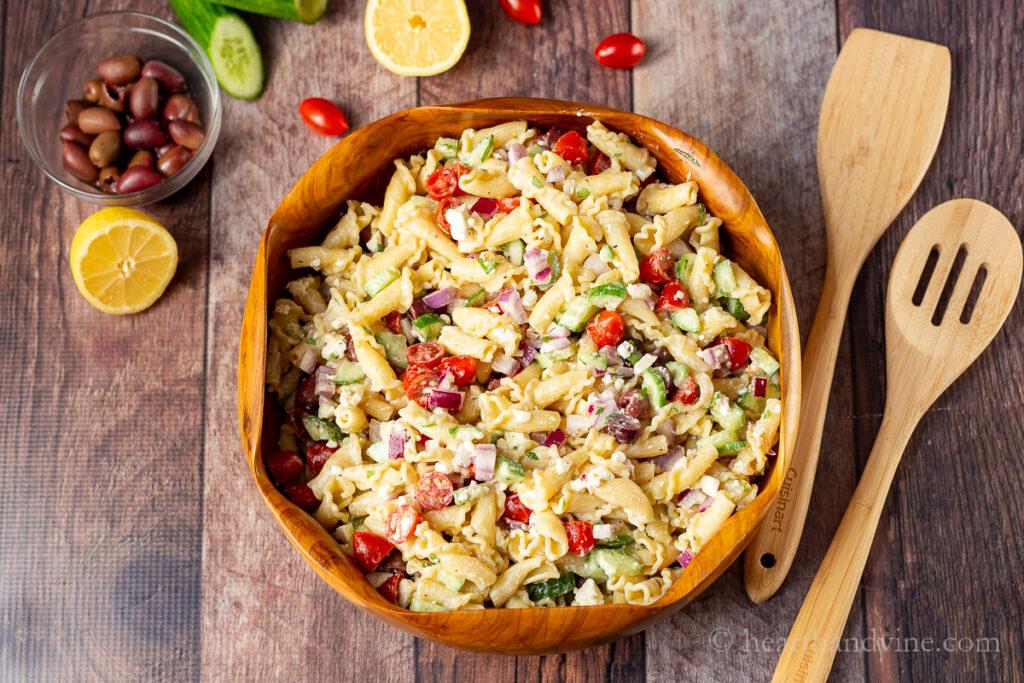 Salada de massa grega em uma tigela de madeira com dois talheres de madeira, limão, tomate uva e pepino e azeitonas ao lado.
