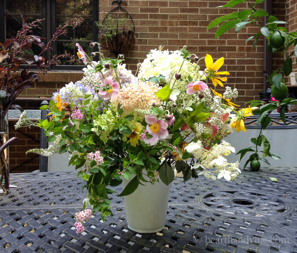 Milk white vase with a large arrangement of cottage flowers such as hydrangea, wind flower, black eyed Susan, and yarrow.