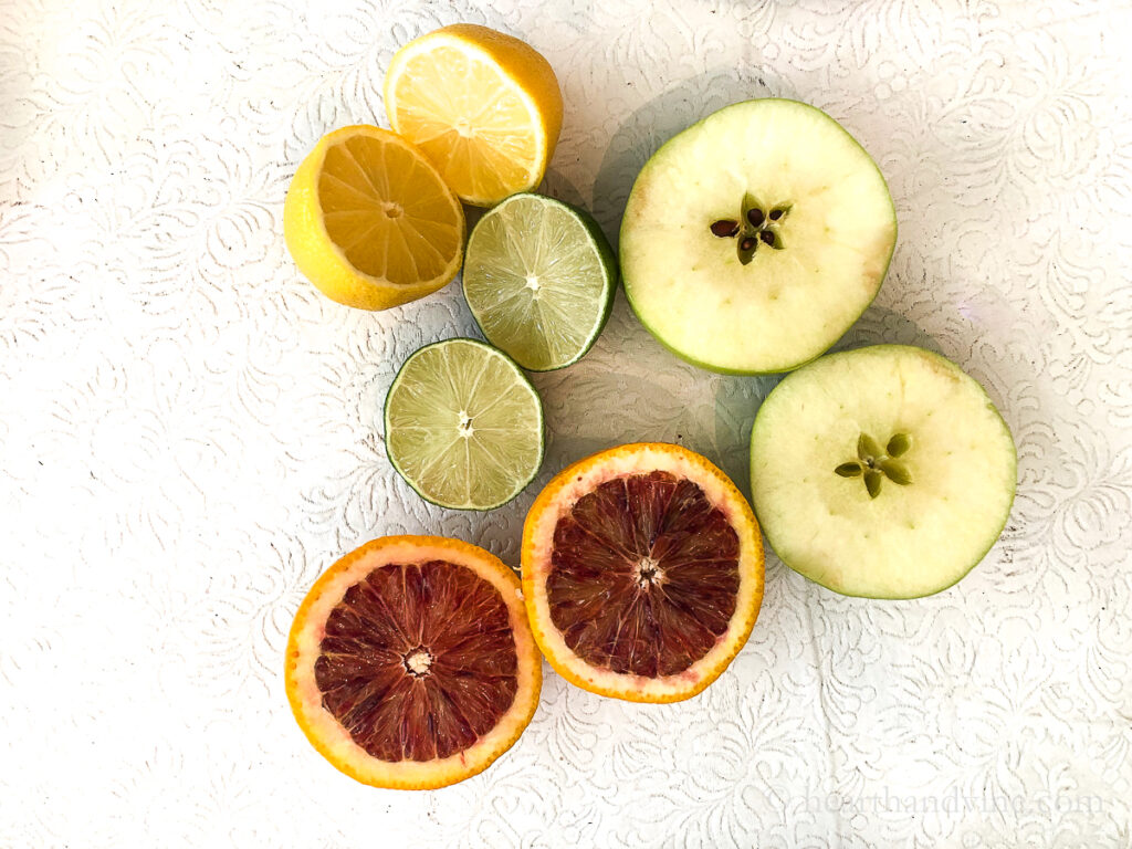 A lemon, lime, blood orange and an apple cut in half on a table.