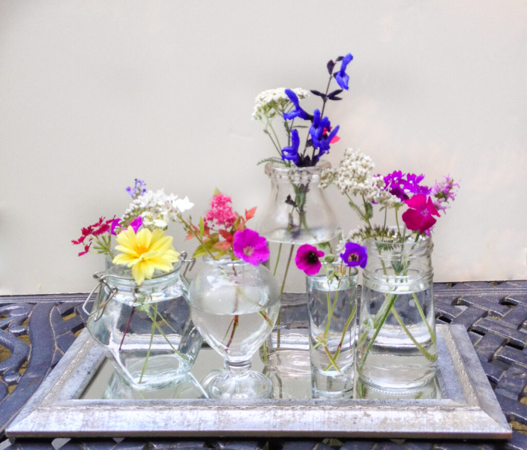 Five small glass vases each with just a few flowers inside.