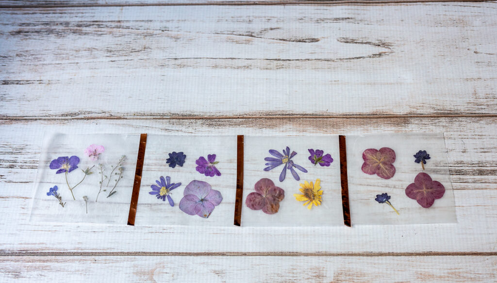 Four wax paper pressed flower parts with strips of metallic tape connecting the sides.